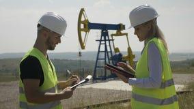 Ingenieurs hulpman die managervrouw informeren die over de vooruitgang van het het werkproject de eenheid van de oliepomp control stock videobeelden