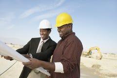 Ingenieurs met Blauwdruk bij Bouwwerf stock fotografie