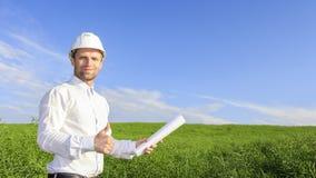 Ingenieursbouwer in witte helm en met blauwdrukken op groene gebiedsachtergrond in heldere zonnige dag royalty-vrije stock fotografie