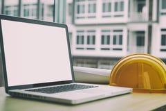 ingenieursbureau met laptop computer, oranje helm, blauwdruk rol Stock Foto's