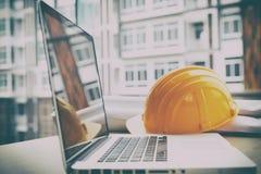 ingenieursbureau met laptop computer, oranje helm, blauwdruk rol Stock Afbeelding