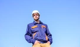 Ingenieurschutzhelmstand vor Hintergrund des blauen Himmels Vorarbeitersteuerbauprozess fremdfirma Stockfotografie