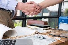 Ingenieurshandenschudden voor succesvolle overeenkomst in bouwplan A royalty-vrije stock foto's