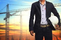 Ingenieursmens die met witte veiligheidshelm tegen kraan werken en Royalty-vrije Stock Afbeeldingen