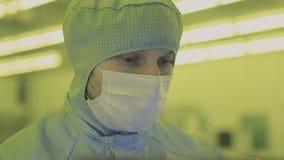 Ingenieurswetenschapper in steriele kostuums, masker zijn in een schone streek bekijkend een proces technologisch geavanceerd fab stock videobeelden