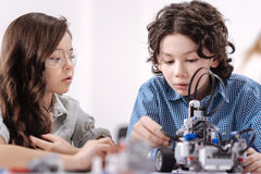 Ingenious kids creating robot at school. Talented science pioneers . Smart crafty involved kids sitting at school and having science lesson while demonstrating Stock Photo