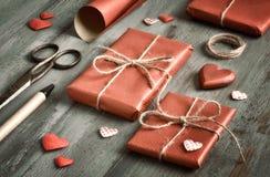 Ingepakt stelt voor, verpakt in rood document met decoratieve harten, c stock fotografie
