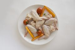 Ingerdients for barbecue: chicken wings and vegetables. Closeup of plate with raw chicken wings. copy space for text Royalty Free Stock Image