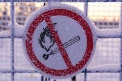 Inget avfyra undertecknar Symbol för öppen flamma för förbud Tecknet täckas med snö Arkivbild