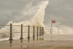 Inget badningtecken som sjögångstormvågor bryter över hamnarmen Arkivbilder