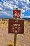 INGET CAMPA I DETTA varnande tecken för OMRÅDE, inget grafiskt tecken för ATV nära svältdelstatsparkbehållare runt om bron över s royaltyfri fotografi
