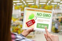 Inget GMO begrepp, flicka rymmer den digitala minnestavlan på suddigt shoppar bakgrund Royaltyfri Foto