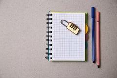 Inget idé eller inspirationbegrepp: lås som ligger på en anteckningsbok och kulöra pennor på en grå bakgrund royaltyfria foton