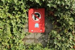 Inget parkera tecken som omges av grönska arkivfoto