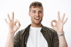 Inget problem fick det Stående av den bekymmerslösa stiliga blonda mannen med borstet och blåa ögon som visar ok gester och att l arkivfoto