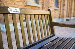 Inget - röka tecknet som fästas på det trä, parkera bänken royaltyfria foton