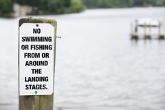 Inget simning eller fiske på sjöteckenstolpen på träbryggapir royaltyfri bild