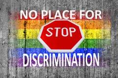 Inget ställe för diskriminering och STOPPtecken och den målade LGBT-flaggan på grå färger hårdnar bakgrund royaltyfri foto