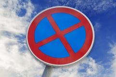 Inget stoppa och inget parkeringstecken på blå baksida för molnig himmel Arkivfoto