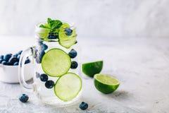 Ingett detoxvatten med gröna det limefruktskivor och blåbäret Med is kall sommarcoctail i exponeringsglasmurarekrus fotografering för bildbyråer
