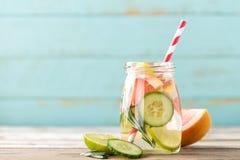 Ingett detoxvatten med limefrukt, grapefrukten, gurkan och rosmarin Arkivbild