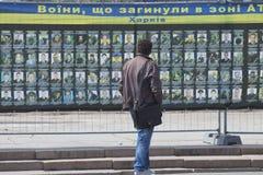 Ingezetenen van de stad dichtbij de tribune met foto's van dode militair Stock Fotografie