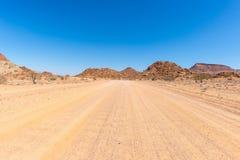Inghiai l'incrocio di strada 4x4 il deserto variopinto a Twyfelfontein, nel Damaraland maestoso Brandberg, destinazione scenica d Fotografia Stock