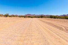 Inghiai l'incrocio di strada 4x4 il deserto variopinto a Twyfelfontein, nel Damaraland maestoso Brandberg, destinazione scenica d Fotografia Stock Libera da Diritti