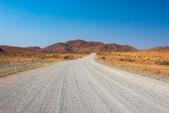 Inghiai l'incrocio di strada 4x4 il deserto variopinto a Twyfelfontein, nel Damaraland maestoso Brandberg, destinazione scenica d Fotografie Stock Libere da Diritti