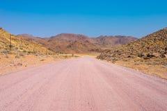 Inghiai l'incrocio di strada 4x4 il deserto variopinto a Twyfelfontein, nel Damaraland maestoso Brandberg, destinazione scenica d Immagini Stock Libere da Diritti
