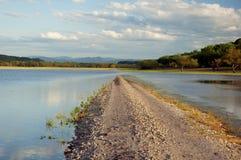 Inghiai la conclusione della strada nel lago. Immagini Stock