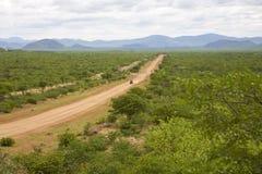 Inghiai la strada con la guida di veicoli 4x4 e le montagne della zebra, Namibi Immagini Stock