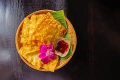 Ingiallisca gli gnocchi fritti e una tazza di salsa su un piatto di bambù al decorato a con l'orchidea disposta sul legno di buio fotografia stock libera da diritti