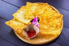 Ingiallisca gli gnocchi fritti e una tazza di salsa su un piatto di bambù al decorato a con l'orchidea disposta sul legno di buio immagine stock libera da diritti