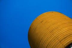 Ingiallisca la costruzione arrotondata di affari con il bello cielo blu in immagine stock libera da diritti