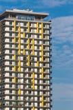 Ingiallisca la costruzione di appartamento colorata a mezzogiorno contro cielo blu immagini stock libere da diritti