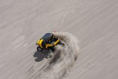 Ingiallisca parallelamente il carrozzino che corre vicino nelle dune di sabbia immagini stock libere da diritti