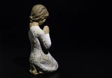 Inginocchiamento di preghiera della scultura isolato su fondo nero immagini stock