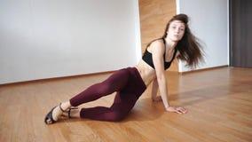 Ingirl da jovem mulher nas calças justas e a parte superior, os saltos altos que encontram-se no assoalho e dança, filme