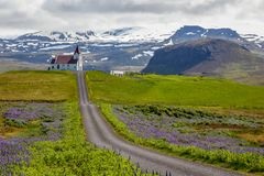 Ingjaldsholskirkja church on the hill, with twisted road in fore. Red roof church on the hill, with summer cottages in the foreground, Vik i Myral, Iceland Royalty Free Stock Image