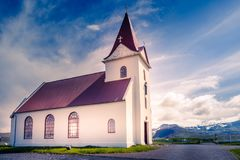 Ingjaldsholskirkja local lutheran church in sunset lights, with. Mountains and glaciers in the background, Hellissandur, Iceland royalty free stock photo