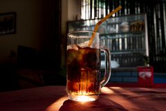 Inglass кокса с соломой Напиток Брайна сверкная с backlight солнца Сверкная питье с льдом в стекле Стоковые Изображения RF