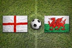Inglaterra contra Bandeiras de Gales no campo de futebol Fotografia de Stock