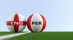 Inglaterra contra Peru Soccer Match - balones de fútbol en los colores nacionales de Inglaterra y de Perú en un campo de fútbol fotografía de archivo libre de regalías