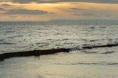 Ingle de madera de la playa semi sumergida por marea en la puesta del sol Cuesta británica fotos de archivo libres de regalías