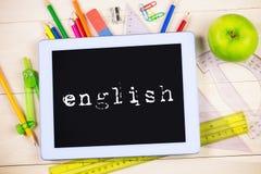 Inglese contro la tavola degli studenti con i rifornimenti di scuola immagini stock libere da diritti