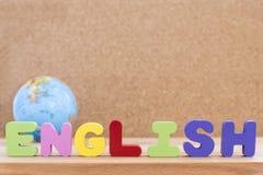 Inglese di parola con il globo sopra fondo di legno Fotografia Stock
