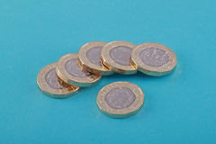 Ingleses novos, Reino Unido moedas de uma libra em um fundo azul Imagens de Stock Royalty Free