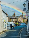 Ingleton in Yorkshire Dales. Ingleton village in Yorkshire Dales with narrow street and rainbow and sign for old sweetie shop stock photos