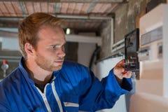 Ingénieur ajustant le thermostat de système de chauffage Images stock